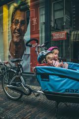 Kids with helmets @ Haarlem (PaulHoo) Tags: street city blue portrait people urban holland color haarlem bicycle shop kids shopping children glasses nikon vibrant candid transport helmet citylife streetphotography nik protection vignette lightroom 2015 streetcandid colorefex d700 analogefex