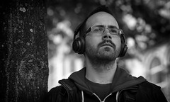 In the Zone (Just Ard) Tags: man glasses spectacles whickers bokeh depthoffield people person face street photography candid unposed black white mono monochrome bw blackandwhite noiretblanc biancoenero schwarzundweis zwartwit blancoynegro  justard nikon d750 85mm headphones