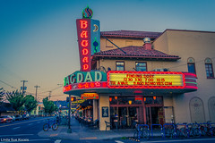 Movie House (Linda Sue Kocsis) Tags: street old blue light sunset red sky moon house cinema color film bike bicycle architecture night oregon america vintage dark movie portland marquee star evening colorful theater neon exterior theatre outdoor dusk sidewalk american lit grainy hawthorne sunnyside bagdad
