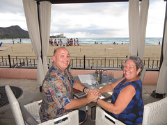 Betty and Barry at their 25th anniversary dinner (BarryFackler) Tags: ocean sea sky food love beach water clouds dinner fence menu table cuisine restaurant hotel glasses evening coast sand couple candles view pacific silverware waikiki oahu anniversary horizon shoreline azure marriage husband landmark betty special celebration event together cabana shore meal diamondhead tropical wife curtains romantic honolulu waikikibeach seashore occasion milestone finedining wineglasses commitment silveranniversary tablefortwo alohashirt royalhawaiianhotel specialoccasion 2015 anniversarydinner 25thweddinganniversary placesettings wickerchairs theroyalhawaiian azurerestaurant bettybowen barryfackler barronfackler bettyfackler