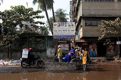 Pedestrians, bikes and motorbikes mix on a flooded street in Kolkata. (Sean Gallagher) Tags: street trees sky india signs men water bicycle trash standing buildings outdoors photography women asia day sitting citylife lifestyle streetscene litter biking pedestrians kolkata flooded motobike westbengal casualclothi