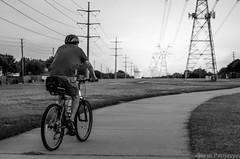 Biking Along The Winding Trail (spanjavan) Tags: red bw man motion male lines evening moving power wheels helmet powerlines trail biker winding grayscale