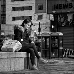 Miles away (John Riper) Tags: street uk england bw woman white news black girl monochrome wall liverpool canon john booth bag square photography mono phone zwartwit candid away thoughts edge l miles contemplating 6d 24105 straatfotografie riper johnriper