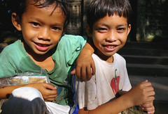 Boys selling postcards (Oakseed) Tags: angkor asia asian backpacking bayon boy brothers cambodia cambodian child childhood children cute destination east friends happy innocence innocent kid minor people poor portrait postcards poverty reap seller selling siem smile smiling southeast tourism travel traveling travelling underage wat work working young youngster youth peddler peddling