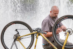 A Fountain Fix (Ian Sane) Tags: ian sane images afountainfix man bicycle flat tire fixing repairing salmon springs fountain downtown portland oregon governor tom mccall waterfront park naito parkway willamette river candid street photography canon eos 5d mark ii two camera ef70200mm f28l is usm lens