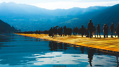 Silhuettes on the piers (Nicola Pezzoli) Tags: blue summer sky people italy lake art tourism water colors sunshine silhouette yellow sunrise canon reflections landscape glow piers floating bergamo brescia lombardia iseo