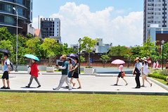 Tourists in the sun (Roving I) Tags: tourists tourism umbrellas grass lawn walking group sunhats protection cloud danang vietnam helicopters museums