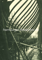 X34119_IV_96 Schiffswerft und Maschinenfabrik Blohm & Voss im Hamburger Hafen - ein Doppelschraubendampfer liegt auf der Helling. Der Schiffsboden ist gelegt, Hintersteven und Spanten sind zu erkennen. (christoph_bellin) Tags: fotos hamburger hafen bilder entwicklung geschichte alte werft historische fotoarchiv bootsbau schiffswerft werftarbeiter