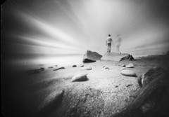 Together (batuda) Tags: pinhole obscura stenope lochkamera film paper altoids tin 6x9 d76 wideangle sea sky clouds motion movement people stones rock shore ground longexposure baltic balticsea coast karkl karkle water wind klaipda analogue analog bw lithuania