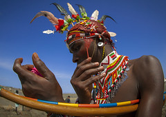 Rendille Tribesman Applying Make Up, Turkana Lake, Loiyangalani, Kenya (Eric Lafforgue) Tags: africa shirtless portrait people flower beauty horizontal closeup painting outdoors person photography mirror necklace day adult kenya african profile feather earring makeup pride tribal headshot jewellery human bead warrior tradition ornate tribe facepaint moran hairstyle samburu cultures paintbrush beautifulpeople preparation adultsonly oneperson miror headdress decorated plasticflower headwear kenyan eastafrica rift traditionalclothing realpeople turkana colorimage onlymen onemanonly waistup colourimage 1people indigenousculture rendille loiyangalani ethny rendile turkanalake colourpicture kenya201407358