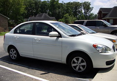 Our Hyundai Accent. (dccradio) Tags: lumberton nc northcarolina robesoncounty car vehicle hyundai accent white tree trees parking parkinglot pavement whiteline hyundaiaccent shadow buildings tire wheels transportation