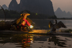 Gas Lamp at Dusk (lycheng99) Tags: light red portrait sky man mountains bird nature water face night reflections river cormorants beard landscape liriver fisherman dusk wing oldman gas gaslamp cormorant raft karst bambooraft cormorantfishing cormorantfisherman ljing karstformation