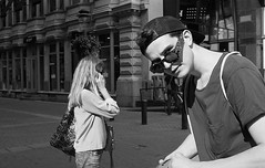 Street scenes (__ _) Tags: people blackandwhite film 35mm eyecontact streetphotography hp5 curiosity ilford journalistic urbanlife selfdeveloped pancakelens konicat hexanon40mm streetinteraction