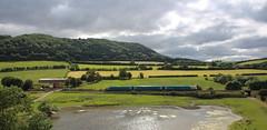 Train in the Shropshire hills (Keith Wilko) Tags: arriva arrivatrains diesel dieseltrains stokesaycastle shropshire shropshiretrains trainsinshropshire pond lake stokesay cravenarms countryside ruralengland englishheritage scenery