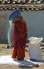 Pouring Rice (cowyeow) Tags: street travel portrait people food woman india house lady composition rural rice candid indian traditional goat farmland goats local preparing khajuraho bandhavgarh madhya