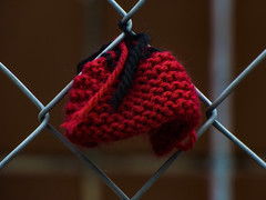 A Bonny Bonnet (Steve Taylor (Photography)) Tags: art fence chainlink red black brown closeup metal newzealand nz southisland canterbury christchurch city cbd bokeh knitting yarnbombing wool bonnet