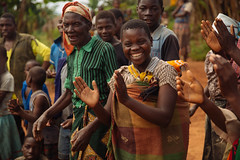 Young Woman with Baby on Back Laughs in a Group of Other Villagers in Malawi (IFPRI-IMAGES) Tags: eastafrica smallholderfarms farm agriculture malawi lilongwe women children girl smile joy celebrate village community baby swaddle carry mother laugh clap fun party gathering