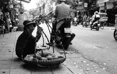 Saleswoman (H_H_Photography) Tags: vietnam travel hanoi asia seasia fruit sales street streetphotography streetphoto candid nikon nikonfe2 fe2 kodak film trix trixpushed pushprocessing 1600 analog streetphotgraphy blackandwhite bw