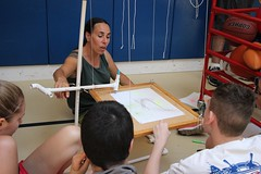 Jen teaching the concept of pendulum by creating a pendulum art board that the students swing under the fixed marker.
