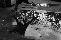 Puddle jump (RM Ampongan) Tags: life street city bw water 35mm puddle photography jump philippines streetphotography human sur activity region bicol irigacity camarines iriga