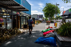 Splashes of Colours (Jocey K) Tags: newzealand christchurch archtiecture buildings trees crane cbd clouds sky rebuild flags people beanbags shadows plants shop