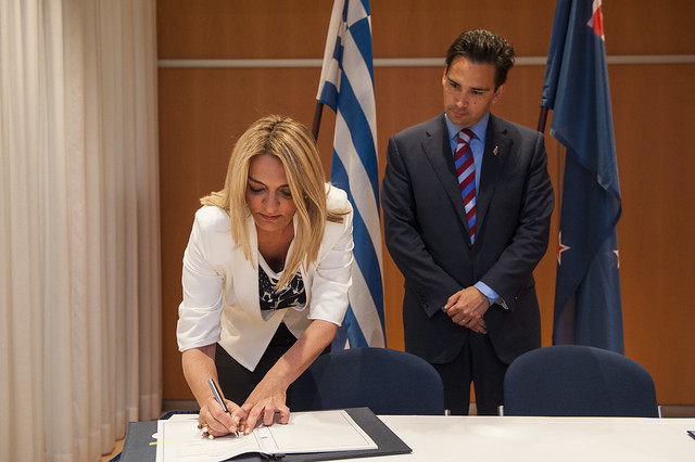 Theopisti Perka and Simon Bridges signing an agreement