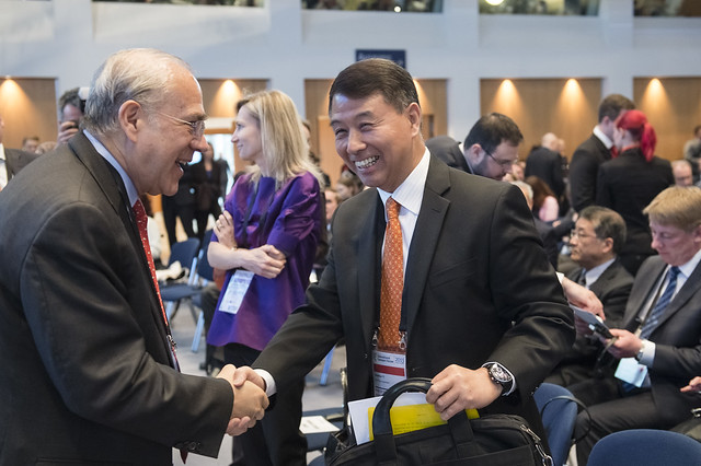 Angel Gurría and Xiaozhun Yi shaking hands