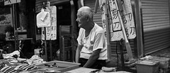 The shopkeeper (Jed Tsui) Tags: bw sony a6300 scissor shopkeeper old sitting anamorphic 2351 opus14 14