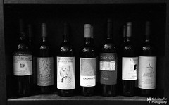Wine Bottles in Rome (Kirk Stauffer) Tags: kirk stauffer photographer adorable amazing attractive awesome beautiful beauty fabulous gorgeous perfect pretty wonderful vino grapes alcohol drink drunk restaurant food eat pantheon neighborhood district roman old ancient rick steves europe grey gray black white bw iphone rack shelf apple seattle
