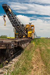Rail Parafinalia by Mossleigh MK-64547  © 2016 (Photo Kubitza) Tags: blue summer sky brown canada black field grass yellow clouds wagon geotagged industrial outdoor rail alberta transportation cumulus prairie geotag cumulusnimbus cranecar passengercar landscapephotography groundtransportation bwcircularpolarizer mossleigh