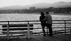 """Aimer, ce n'est pas se regarder l'un l'autre, c'est regarder ensemble dans la mme direction""...........  Antoine de Saint-Exupry (Phoebus58) Tags: california sea blackandwhite mer love monochrome bench evening pier losangeles couple noiretblanc santamonica olympus soir banc amoureux"