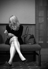 Waiting... (tim.perdue) Tags: waiting woman girl person figure seated legs crossed bench purse wall window carpet shoes heels hair black white bw monochrome candid street portrait
