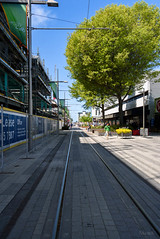 At the End of the Line (Jocey K) Tags: trees newzealand christchurch sky people architecture buildings shadows flags rebuild tramlines containermall restartmall