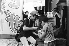 Yanaka, Tokyo (fabiolug) Tags: kids kid children child eating yanaka people street streetphotography tokyo japan japanese asia leicamp leica mp rangefinder film filmphotography believeinfilm blackandwhite blackwhite bw kodaktrix400 trix400 kodak trix kodaktrix leicaelmarit28mmf28asph elmarit28mmf28asph elmarit28mm leicaelmarit28mm 28mm elmarit leicaelmarit wide wideangle spoon