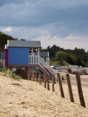 Beach huts. (CraftyBev) Tags: beach huts sand posts clouds trees norfolk east anglia uk