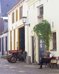 Man and tractor, together outside (andzwe) Tags: deventer man bench tractor trekker street portrait countingmoney oudemosterdfabriek 58 walstraat