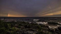 Dark Rainbow (NightSkyMN) Tags: water minnesota rainbow rocks waves rays tofte radiatinglight lakesuperiorcookcounty