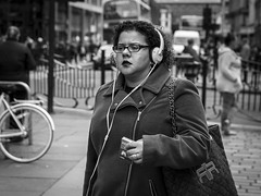 Blissful Ignorance (Leanne Boulton) Tags: people monochrome urban street candid portrait portraiture streetphotography candidstreetphotography candidportrait streetlife woman female face facial expression look emotion feeling isolation smoker cigarette earphones tone texture detail depthoffield bokeh natural outdoor light shade shadow city scene human life living humanity society culture canon 7d 50mm black white blackwhite bw mono blackandwhite glasgow scotland uk