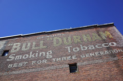 """Bull Durham"" (Eric Flexyourhead (shoulder injury, slow)) Tags: porttownsend jeffersoncounty wa washington usa downtown madisonstreet waterstreet madisonwater building old wall brick mural weathered worn faded tobacco smokingtobacco bulldurham sky clear blue ricohgr"