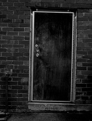 Waiting outside (sally_tregear) Tags: urban blackandwhite streets buildings doors bricks melbourne walls lanes allyways