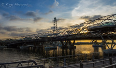 Urban landscape (kingamesaros) Tags: singapore cityscape bridge helix sunrise marinabay canon outdoor waterfront clouds sun ray yellow morning city