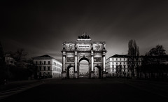 The Gate to the City (One_Penny) Tags: street city longexposure trees sky urban blackandwhite bw white house black building architecture clouds canon germany dark munich münchen bayern deutschland bavaria photography town gate fineart wideangle siegestor 6d ndfilter victorygate leopoldstrase