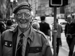 Happy To Help (Leanne Boulton) Tags: people monochrome depthoffield urban street candid portrait portraiture streetphotography candidstreetphotography candidportrait streetlife eyecontact candideyecontact old age aged elderly man male face facial expression gentleman war veteran volunteer helpful smile smiling happy happiness event festival edinburghfringefestival fringefestival2015 tone texture detail bokeh beret uniform natural light shade shadow city scene human life living humanity society culture art canon 7d 50mm black white blackwhite bw mono blackandwhite scotland uk edinburgh
