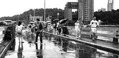 A scene (Tricycl) Tags: fujifiljm fuji x70 people street photo photography candid shot spontaneous laugh laughter fight tourists umbrella reflection rainy day rain blackandwhite black white