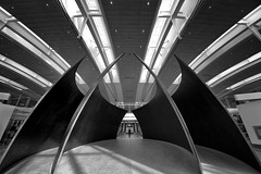 Bat Signal in the Toronto Departures Lounge (departing(YYZ)) Tags: travel shadow blackandwhite sculpture toronto canada monument statue architecture person lights airport sony lounge symmetry transit batman northamerica ultrawide 14mm samyang torontopearsonairport