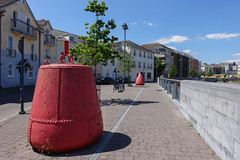 Buoys on the Street (gabi-h) Tags: waterford street railing wall fence buoys red blue sky river gabih architecture buildings clouds benches lightstandards windows cobblestones sidewalk trees