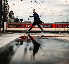 puddle jump (ewitsoe) Tags: reflection ewitsoe nikond80 35mm street wet water man polish polska city rails puddles summer tram rain ciitylife raining reflected reflect mirror double urban model