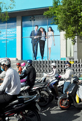 Different strokes (Roving I) Tags: billboards images business motorscooters traffic street saigon hcmc hochiminhcity helmets facemasks gates trees vertical vietnam contrast