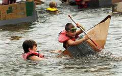 May Day...May Day! (Poocher7(Away until September,sometime)) Tags: river children lifejackets sinking cardboatraces fun summer sports watersports oar splashing spray water sinkingship boat maydaymayday booyah portrait candid people goggles tryinghard
