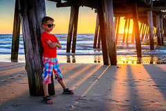 Boy standing on the beach under pier at sunset (spotandshoot.com) Tags: adelaide australia horizontal people relaxation summer travel vacation aussie beach boy casual caucasian child childhood concept copyspace day emotion face fashion hands jetty kid lifestyle look male natural ocean one outdoor person pier portrait red relaxed relaxing rest resting sand sea shore standing star sunglasses sunlight sunset tshirt